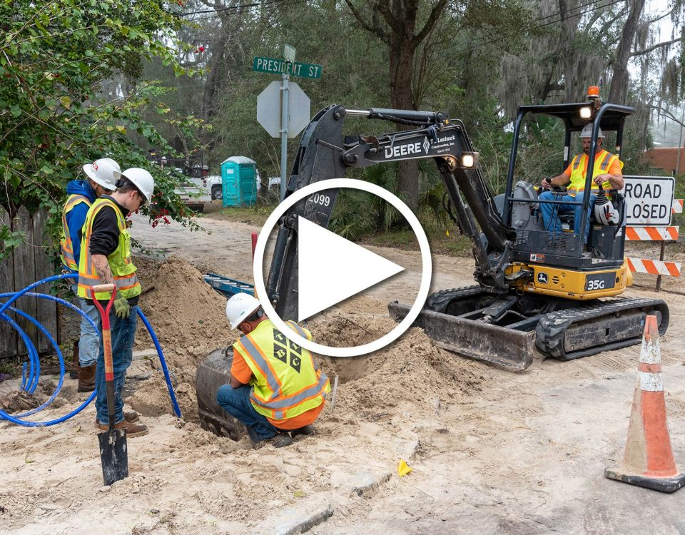 Four district employees working it a hole to fix water pipes