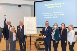 Governign board members with poster sized water conservation month proclamation