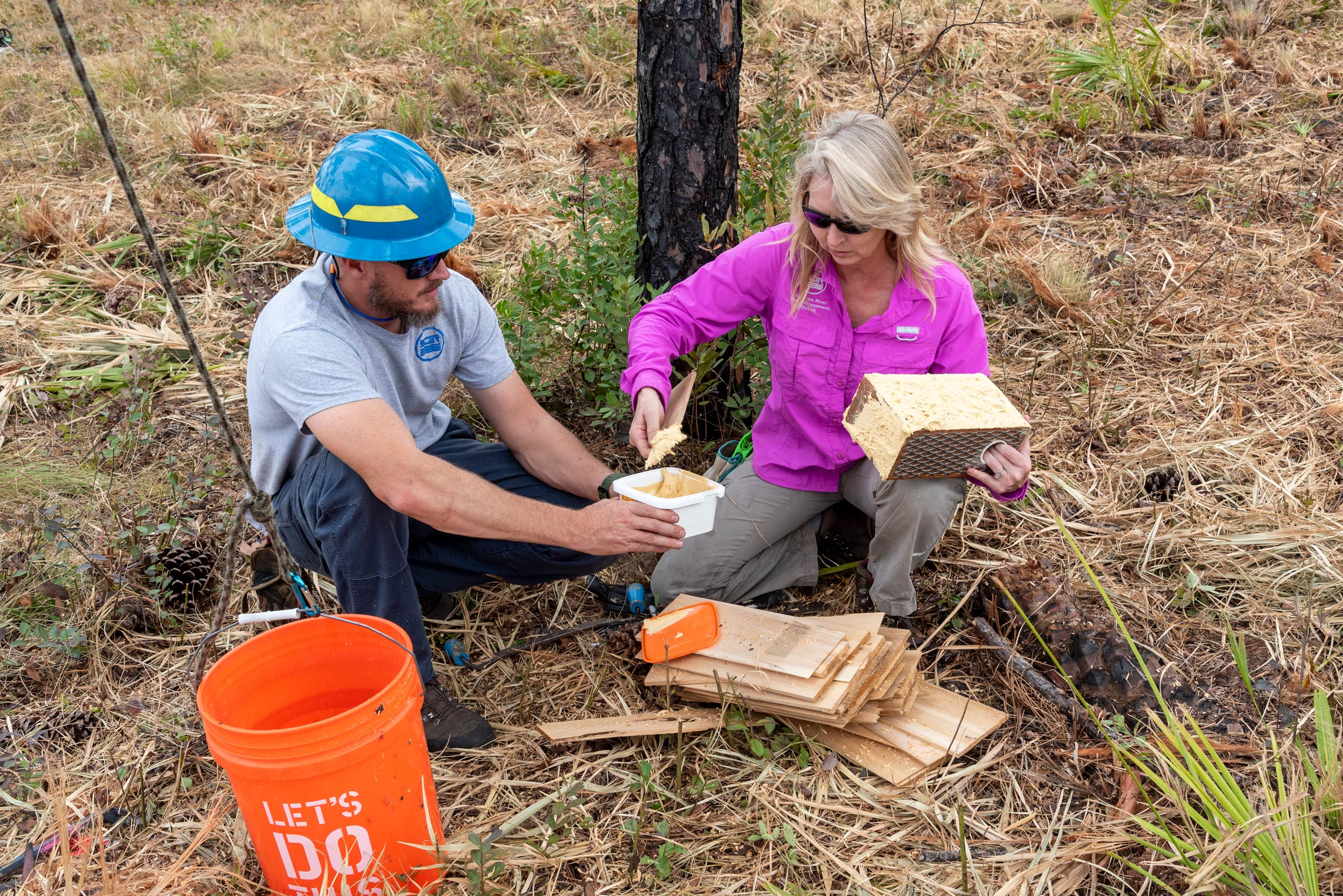 District staff members add glue to the outside of a woodpecker box to prepare it for placement in a tree.