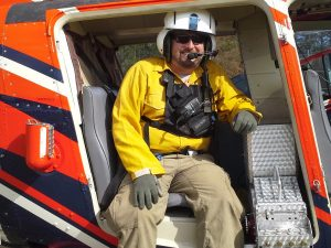 Graham Williams prepares to lift off to ignite a prescribed fire in a remote area from a helicopter.