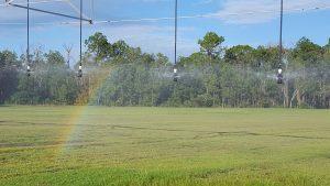 A small rainbow on a farm field