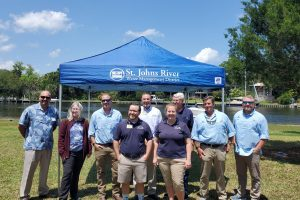 District staff and board members standing in front of a portable tent