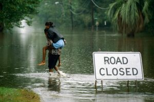 A person carying someone through highwaters