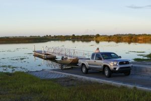 Man using a Toyota truck to load a small pontoon boat
