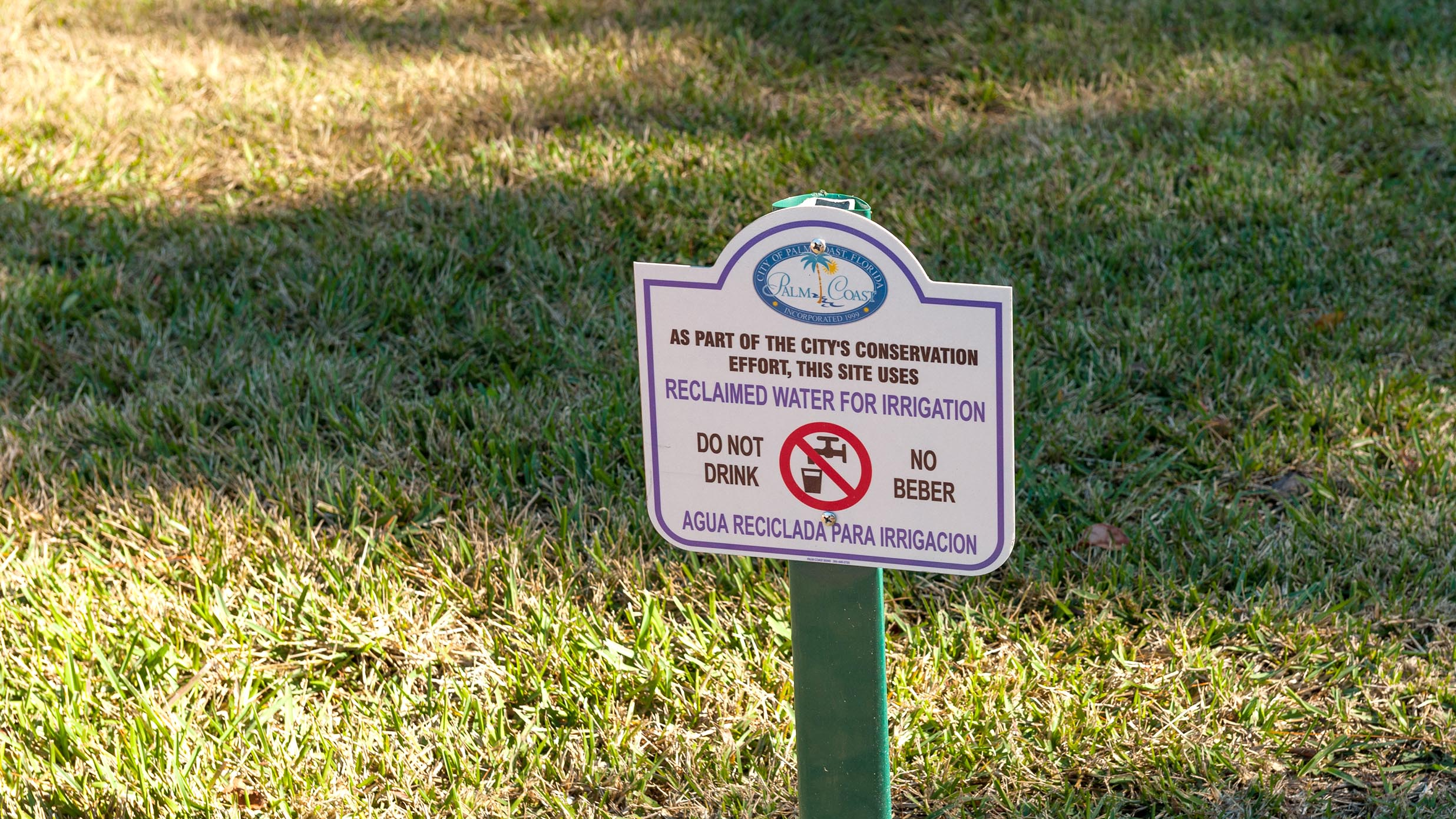 """""""Don't drink"""" sign on a grass lawn"""