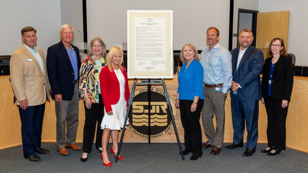 Governing board members standing next to a declaration