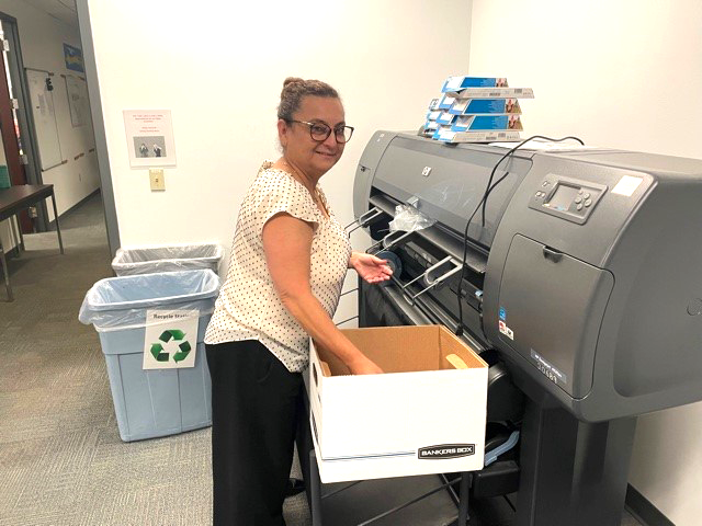 District employee packs materials in the copier room