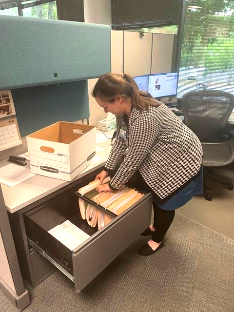 District employee organizes files and prepares to box them for her move