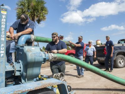 District staff setting up a portable water pump after Hurricane Matthew