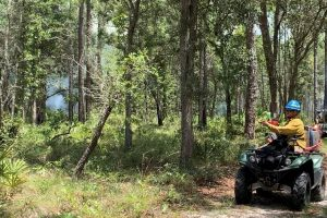 Person on ATV controlling a prescribed fire with water