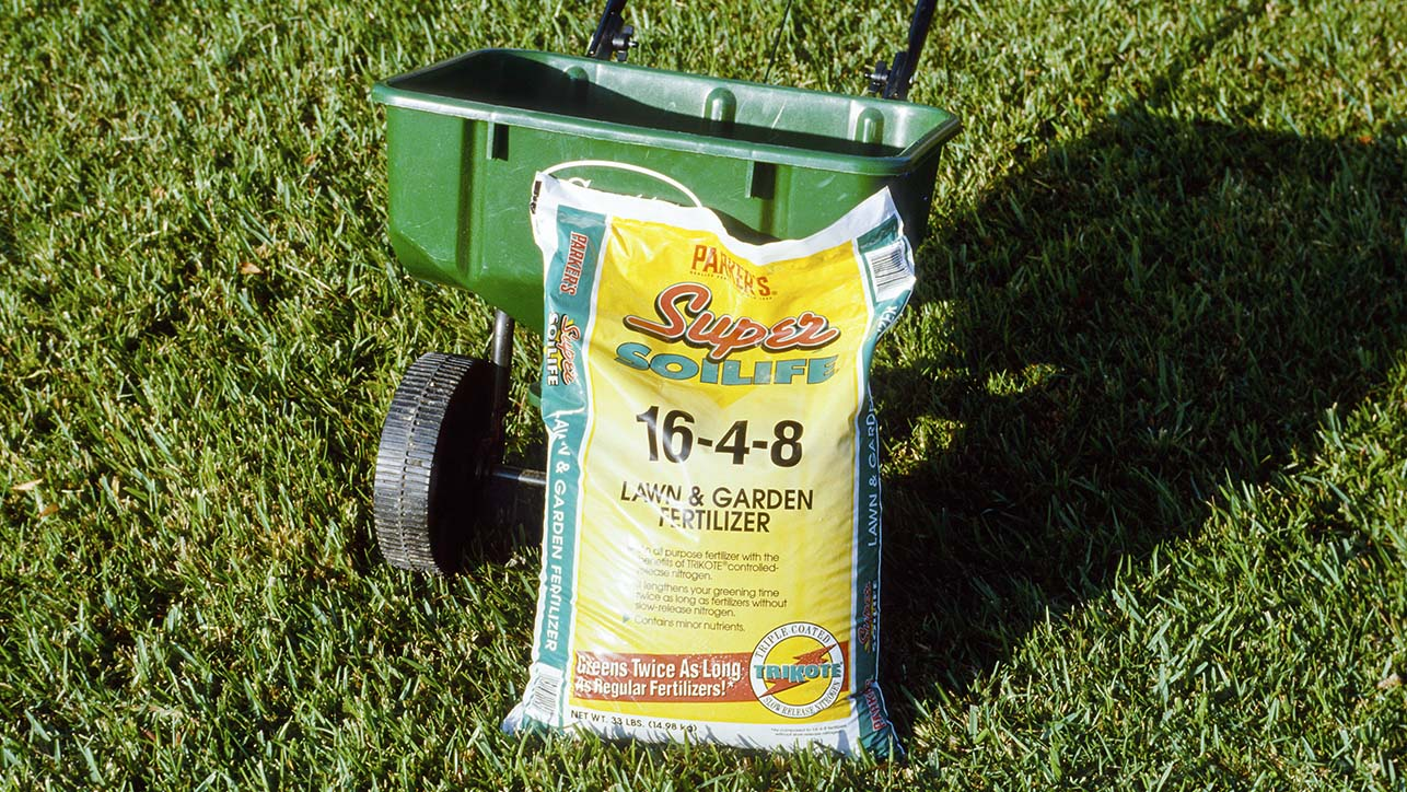 A bag of fertilizer leaning against a fertilizer spreader