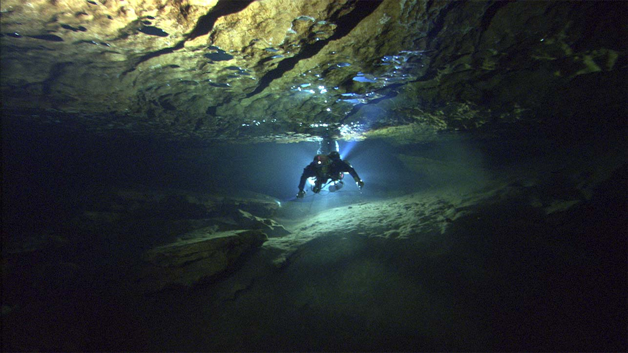 A single diver swimming in a cave