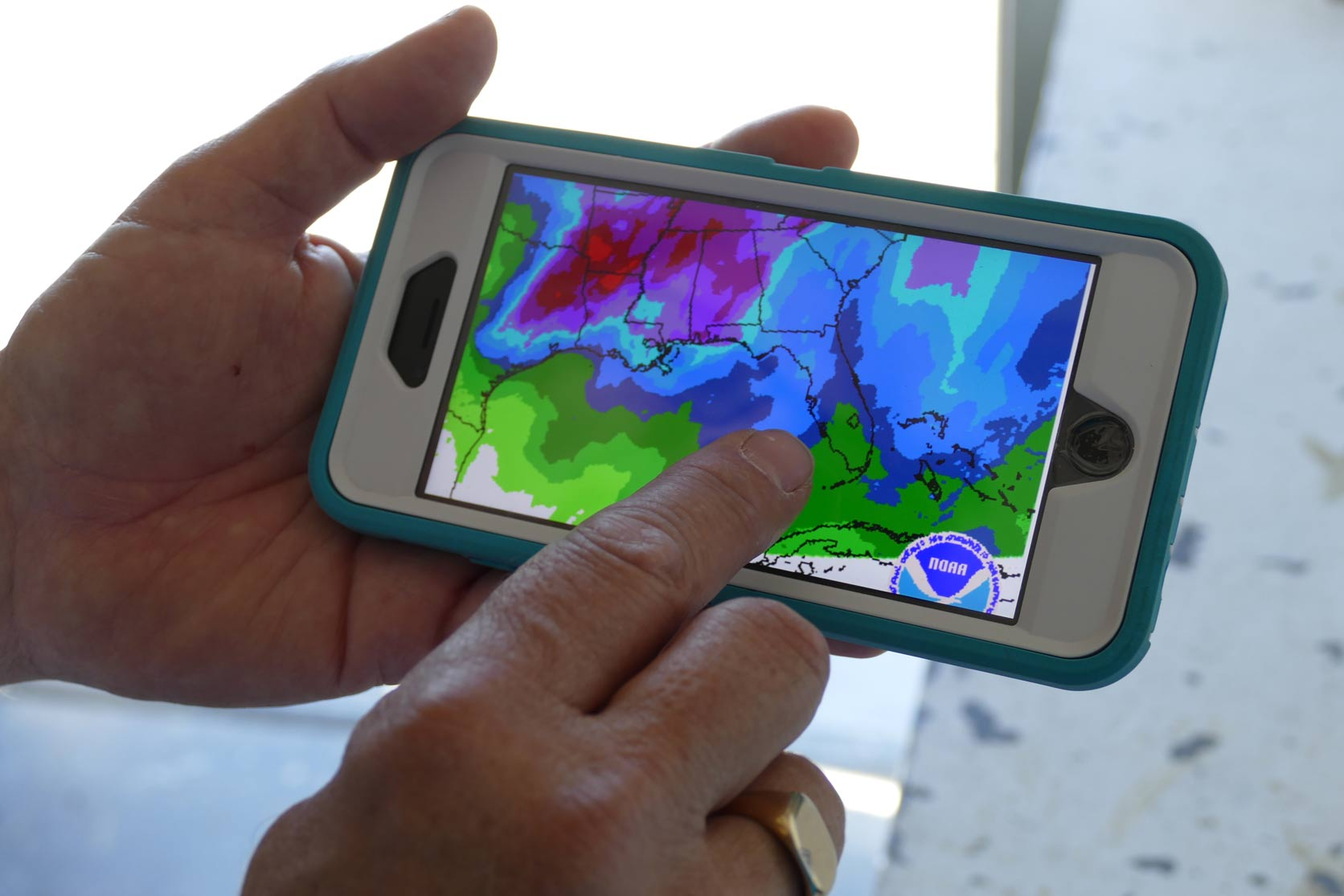 Person tapping a cell phone showing weather