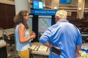 Two people talking in front of a display about water supply planning