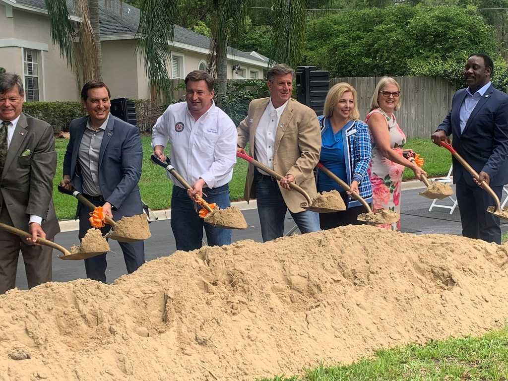 People with shovels standing behind a pile of sand