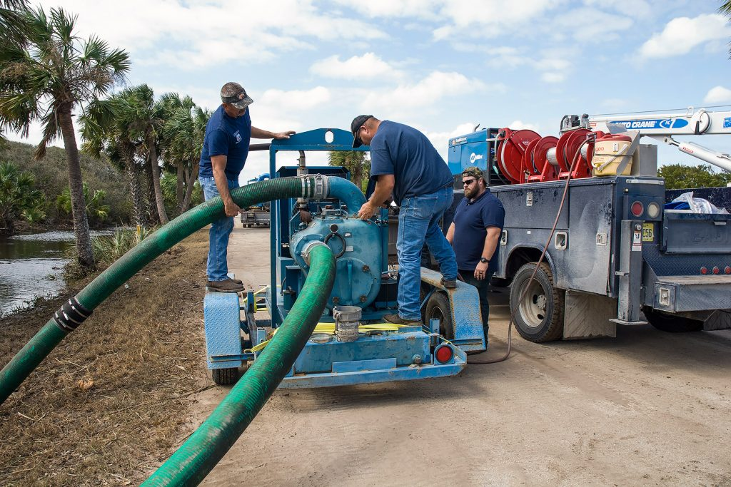 People working with a large water pump