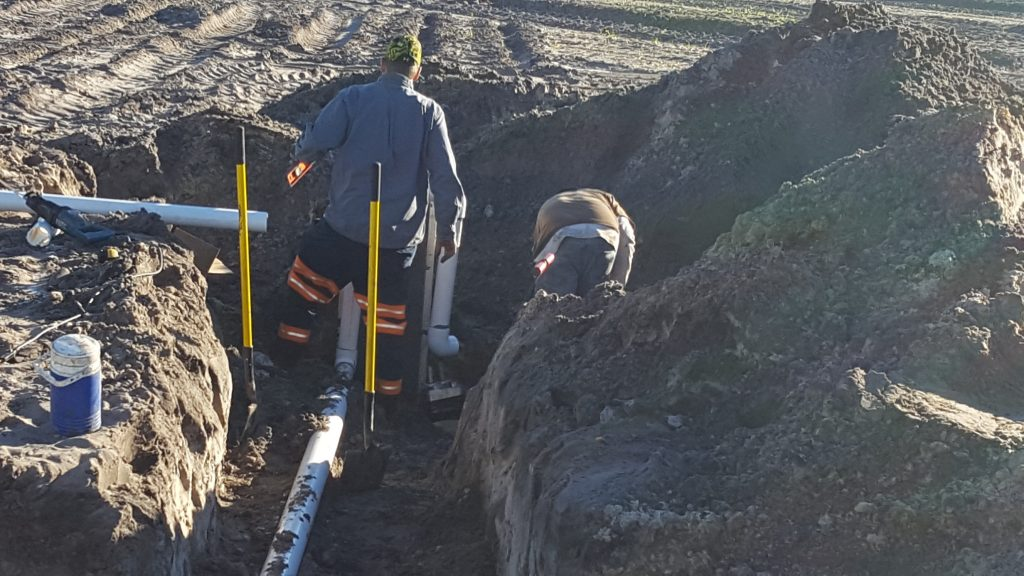 Workers putting down pipes in a trench
